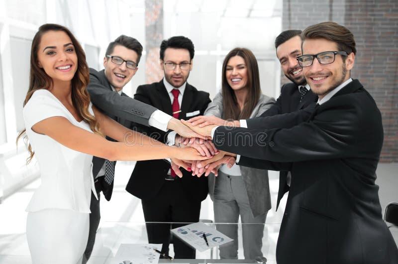 Verbindungshände des glücklichen Geschäftsteams zusammen stockbilder