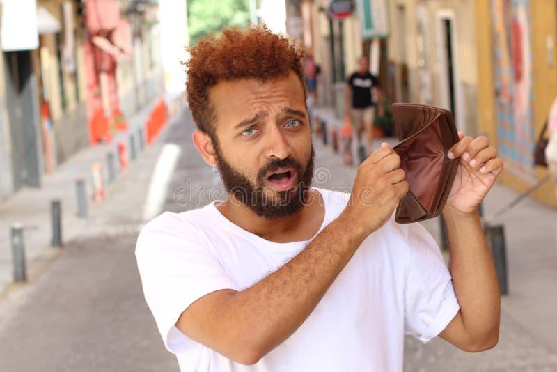 Verblüffter Mann, der seine leere Geldbörse hält stockfotos
