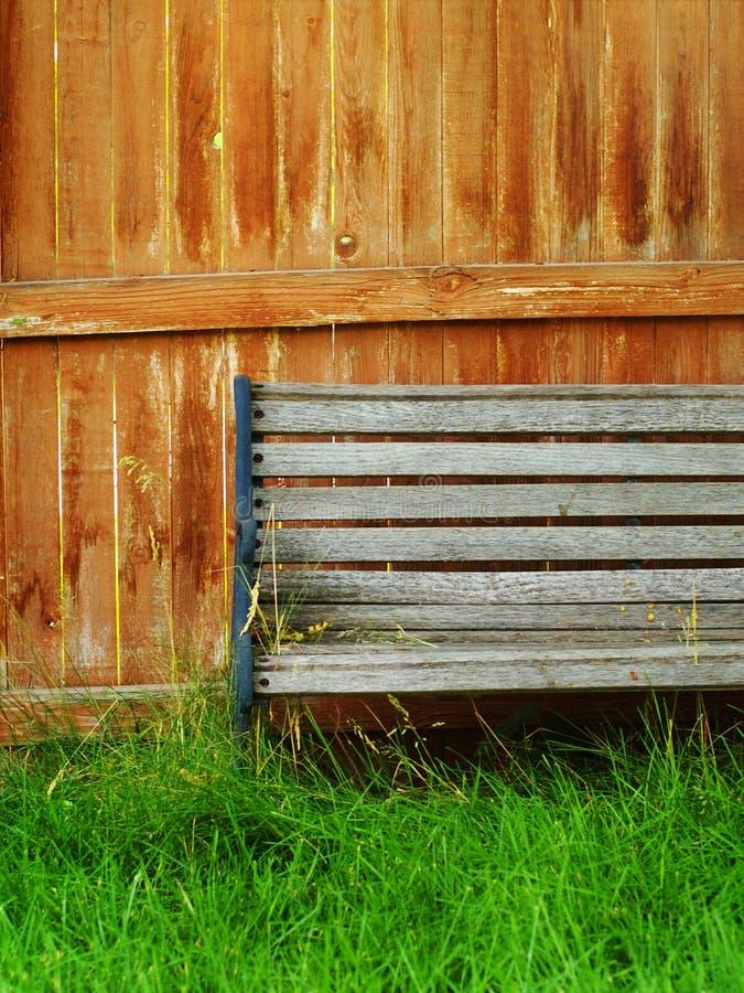 Verblassene hölzerne Bank, Zaun und Gras stockfotos