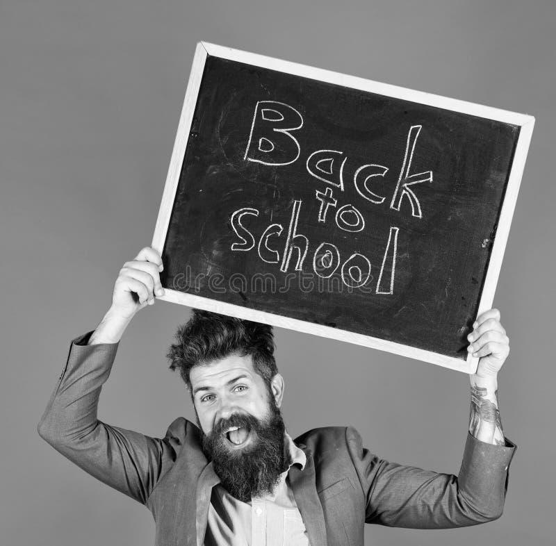Verblijfspositief Houdt de leraars gebaarde mens bord met inschrijving terug naar school blauwe achtergrond Leraar met stock foto