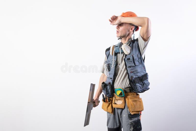 Verbonden bouwer met spatel In werkkleding en harde hoed Op een lichtgrijze achtergrond royalty-vrije stock afbeeldingen