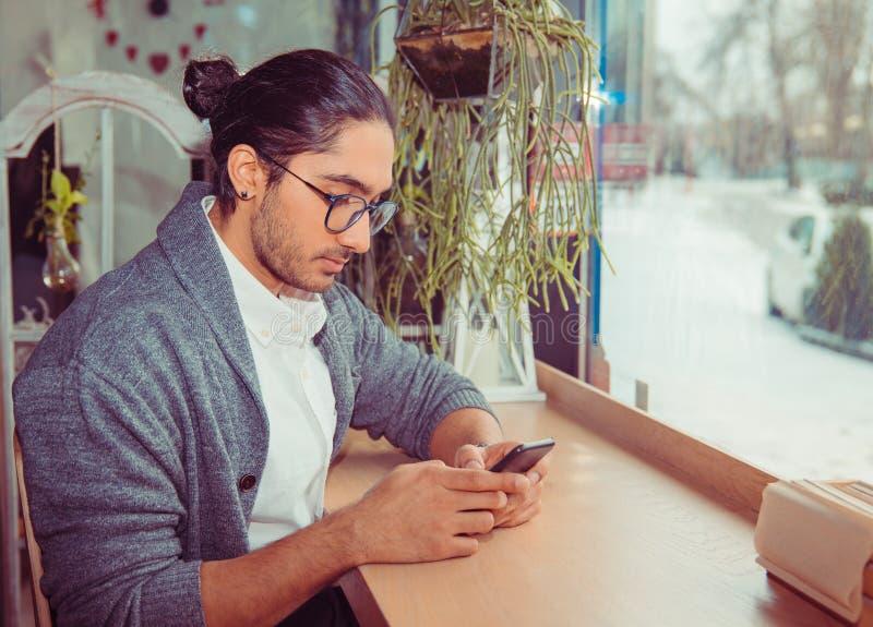 Verbonden het blijven Gelukkige jonge mens die zijn mobiele telefoon bekijken stock afbeeldingen