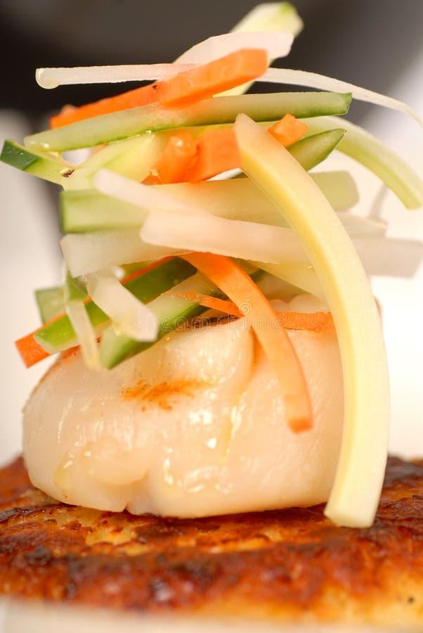 Verbrannte Kamm-Muschel mit Gemüse auf Befestigungsklammerkuchen lizenzfreies stockbild