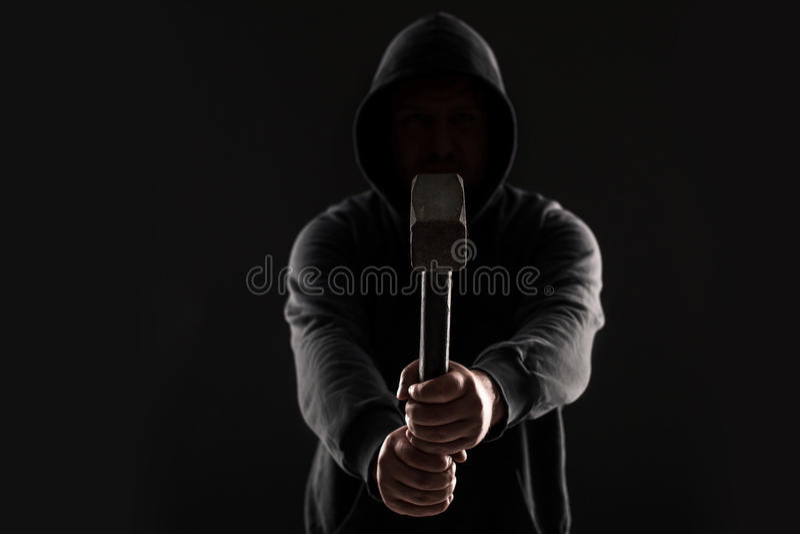 Verbrecher in der dunklen Kleidung und im Kopfschutz mit Hammer stockbild