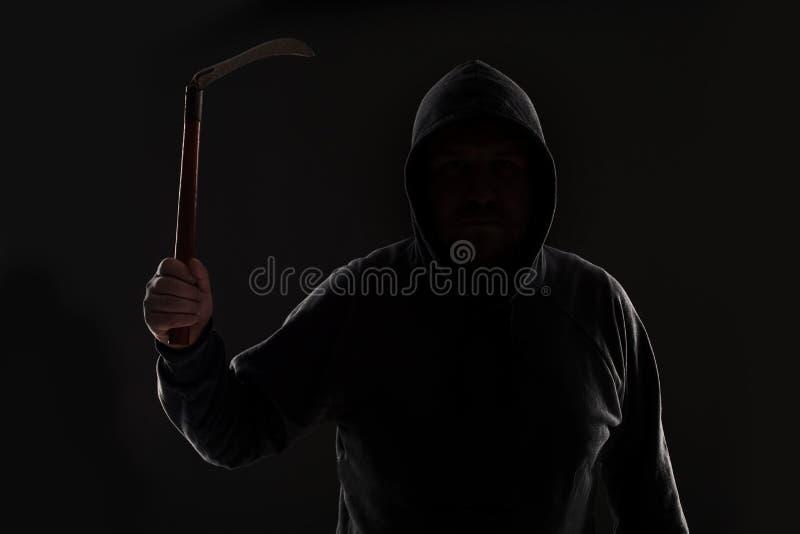 Verbrecher in der dunklen Kleidung und im Kopfschutz mit Sense stockfoto