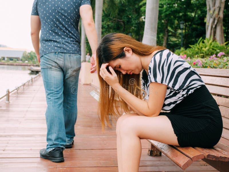 Verbreken van een paar met droevige meisje en vriend die met stad op de achtergrond er vandoor gaan stock fotografie