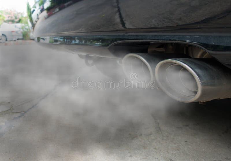Verbrennung dampft, aus schwarzes Autoauspuffrohr, Luftverschmutzungskonzept herauskommend stockfotografie