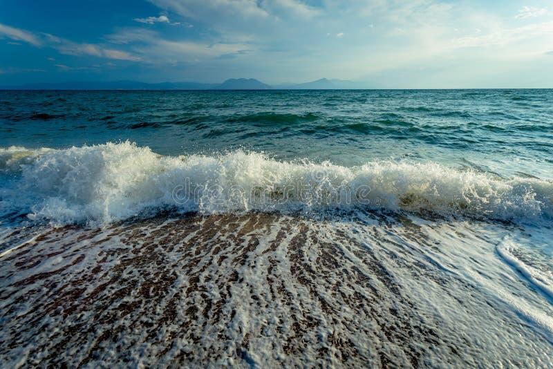 Verbrijzelende Golven op Grieks Sandy Beach op Helder Sunny Day During de Vakantie stock afbeelding
