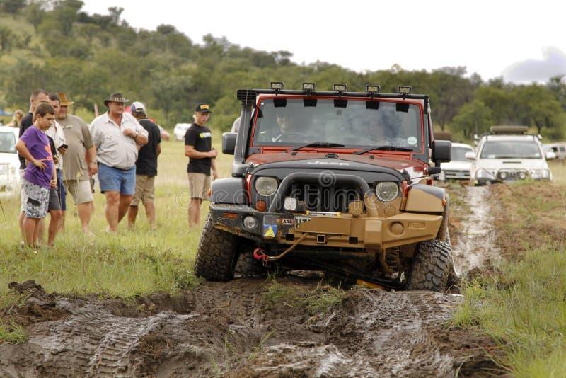 Verbrijzeling Beige Jeep Rubicon die modderhindernis kruisen royalty-vrije stock foto