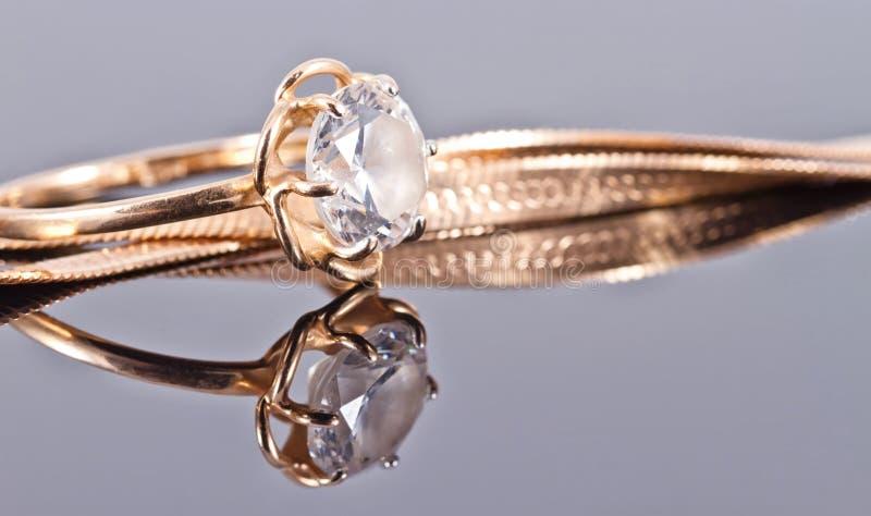 Verdünnen Sie empfindlichen Goldring mit Diamant- und Goldkette stockfotos