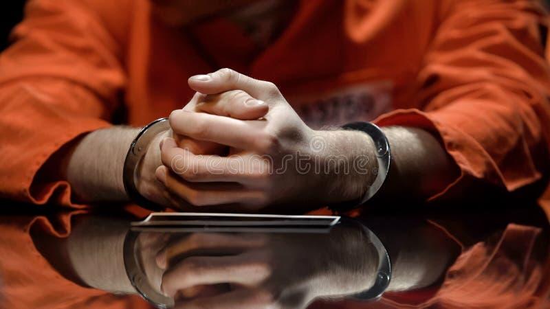Verdacht in handcuffs die op foto letten, die met politie in onderzoek samenwerken stock foto