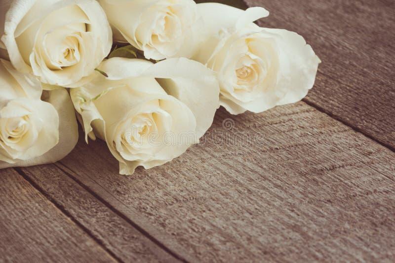 Verdaderas rosas blancas suaves como fondo neutral en el tablero de madera Foco selectivo fotos de archivo