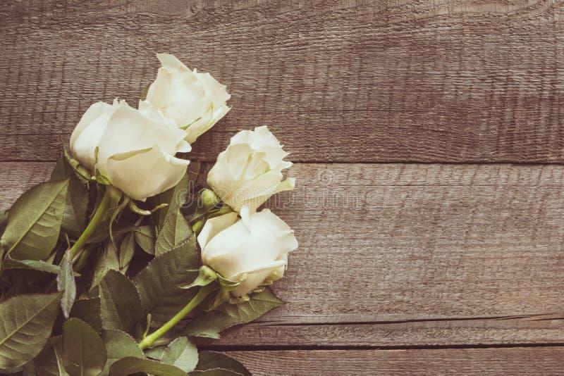 Verdaderas rosas blancas suaves como fondo neutral en el tablero de madera Imagen entonada Visión superior foto de archivo