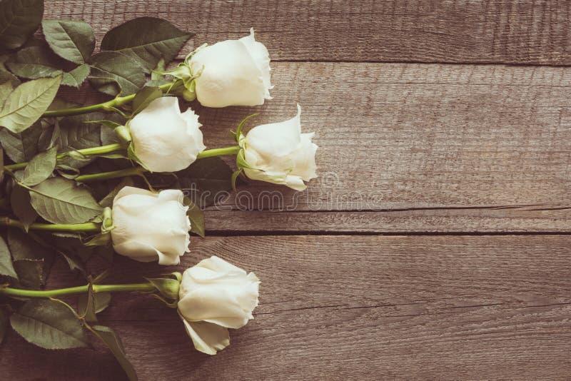 Verdaderas rosas blancas suaves como fondo neutral en el tablero de madera Imagen entonada Visión superior fotos de archivo