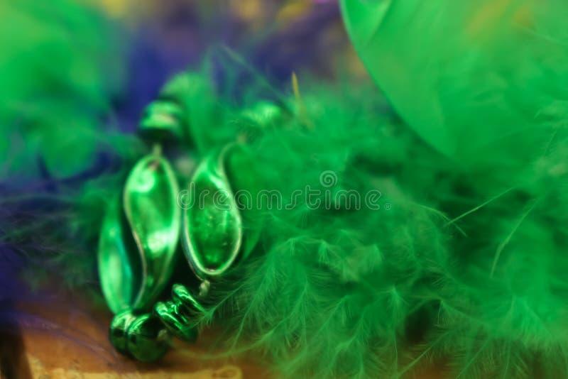 Verde colorido y la púrpura empañaron el fondo de Mardi Gras con las plumas y las gotas fotografía de archivo