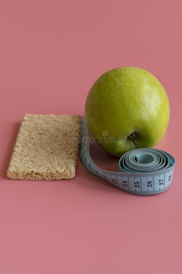 Verde de dieta Apple del concepto y cintura en un fondo rosado Foto vertical imagen de archivo libre de regalías