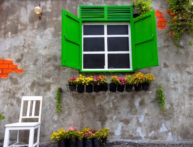 Verde de la ventana en una casa vieja adornada con las macetas y las flores con una silla blanca en fondo del muro de cemento fotos de archivo