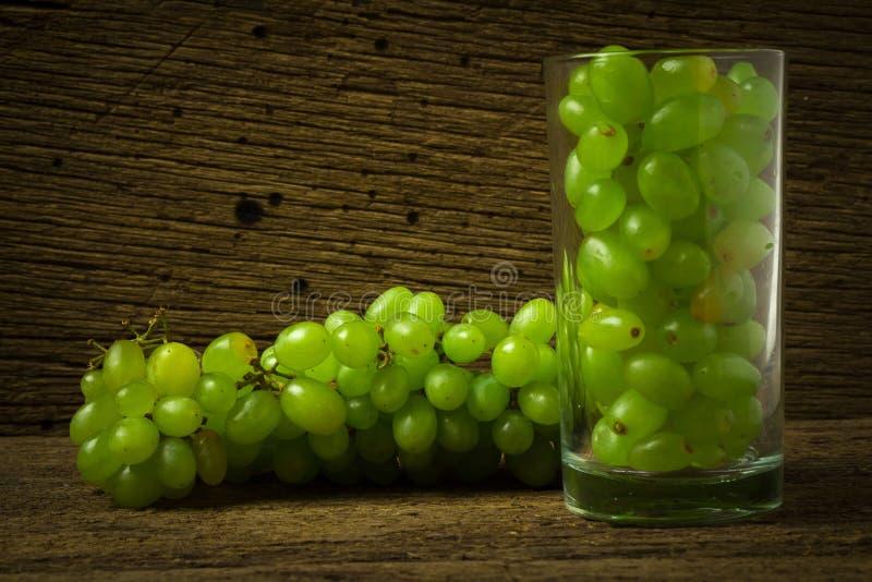 verde de las uvas en madera vieja de OM del vidrio fotos de archivo libres de regalías