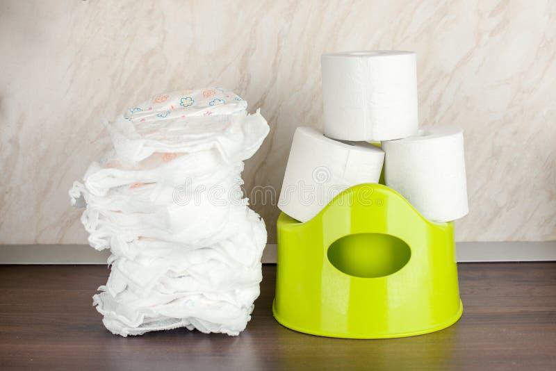 Verde del pote del retrete del ` s de los ni?os, panales y papel higi?nico, el concepto de la transici?n del ` s del beb? de los  imagen de archivo