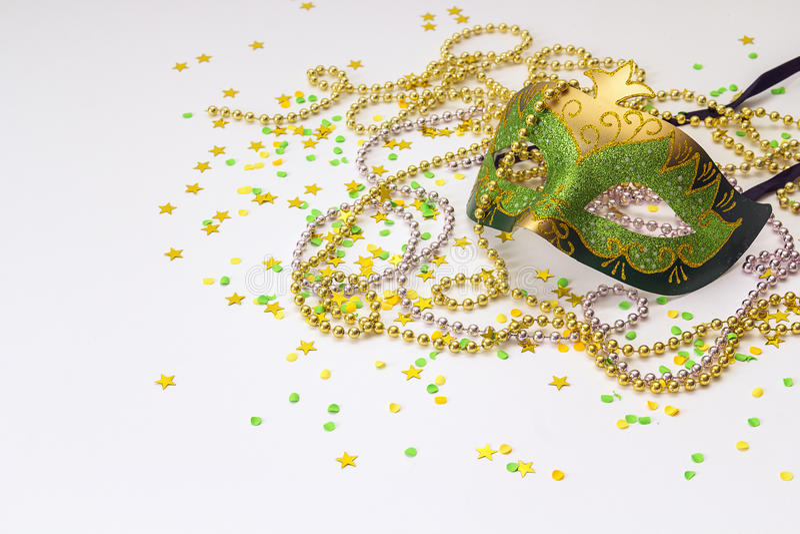 Verde do carnaval e máscaras e grânulos do ouro em um fundo branco imagens de stock