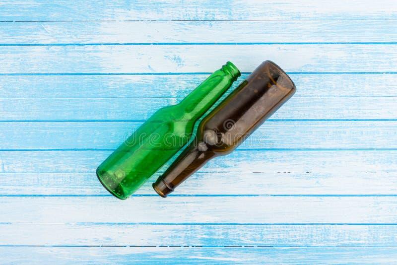 Verde e bottiglie di birra vuote di Brown sulle sedere di legno dipinte bianco blu fotografia stock