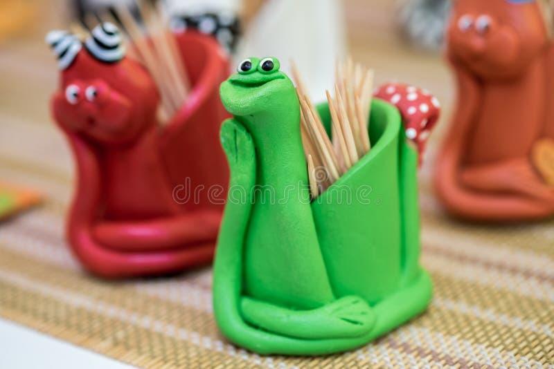 Verde engraçado da serpente e suporte feito a mão vermelho do palito foto de stock