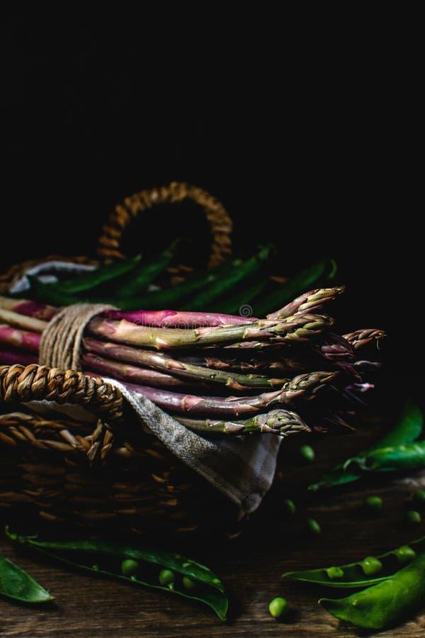 Verde fresco y espárrago púrpura, guisantes verdes en la cesta de mimbre, luz dura, sombras profundas, fondo oscuro - alimento  foto de archivo libre de regalías