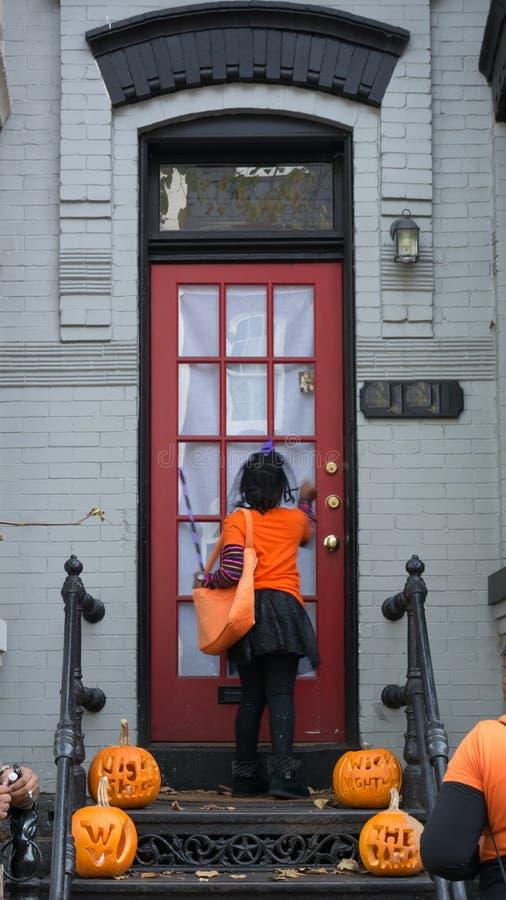 Verdecktes kleines Mädchen, das eine Tür bittet um Herzchen während ha klopft stockfotografie