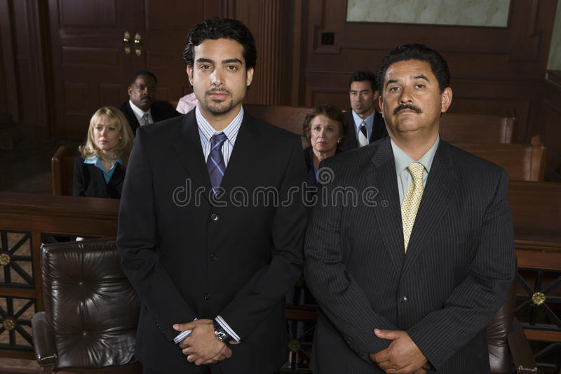Verdediger Standing With Client in Rechtszaal stock afbeelding