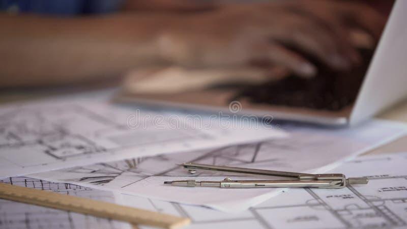Verdeler en heerser die op flatlay-outs liggen, architect die aan laptop PC werken stock fotografie