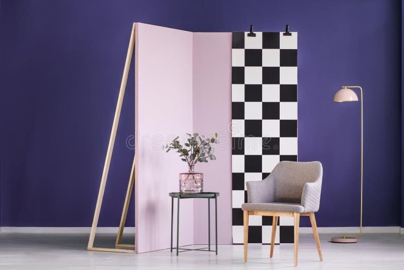 Verdelingsmuur met geruit die patroon in een purpere ruimte wordt geplaatst inter stock fotografie