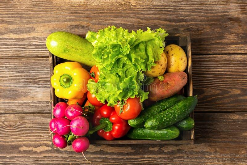 Verdes de las verduras frescas en una caja en un fondo de madera Disposici?n plana de la cosecha del oto?o Visi?n desde arriba Co fotos de archivo libres de regalías