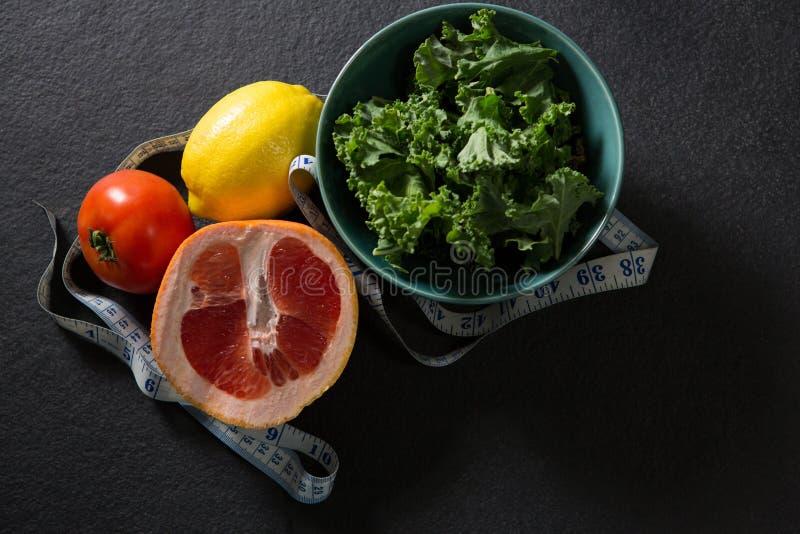 Verdes de mostaza en cuenco con la fruta cítrica, el tomate y la cinta métrica ilustración del vector