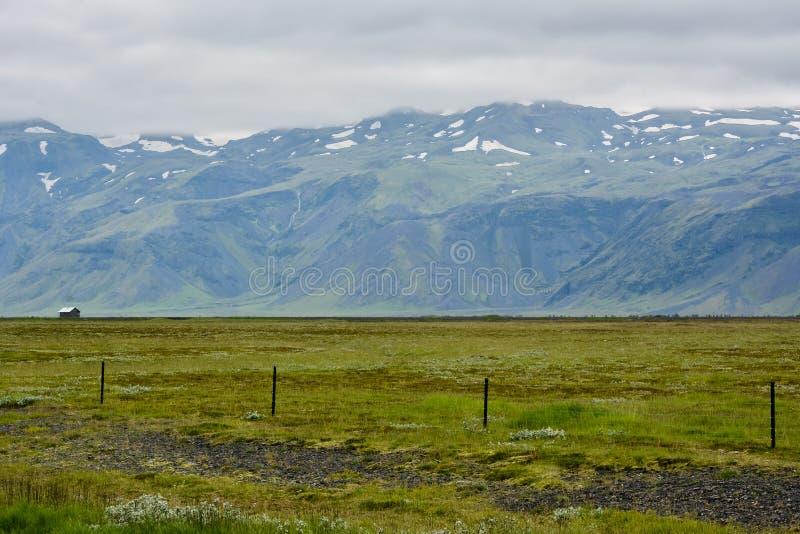 Verdes enormes esvaziam o campo com vista à montanha e à casa pequena imagens de stock