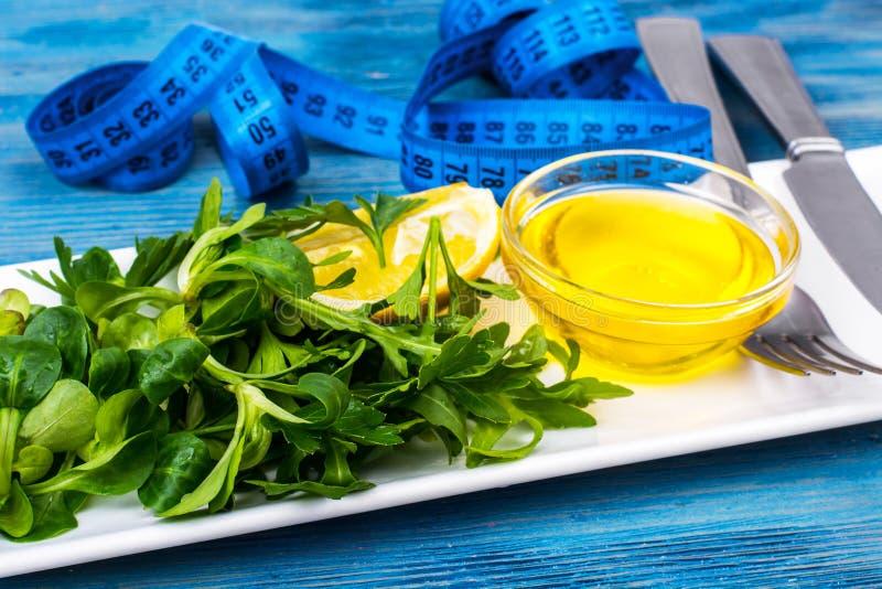 Verdes frescos, ensalada, aceite de oliva, limón-concepto de nutrición dietética imagenes de archivo