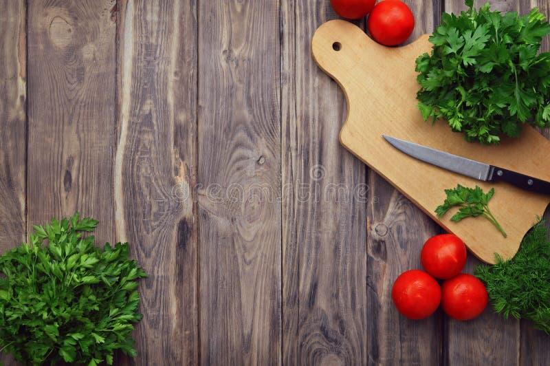 Verdes frescos, vegetais e utensílios de cozimento em um fundo de madeira Configuração lisa Vitaminas verão Dieta Vegetariano ou  imagens de stock