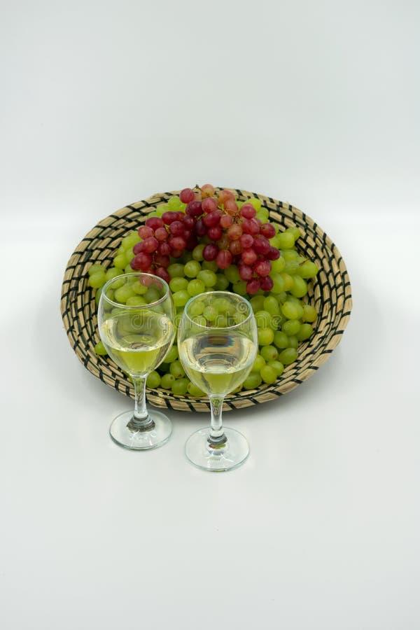 Verdes frescos y uvas rojas en una cesta con las copas de vino blancas imagenes de archivo