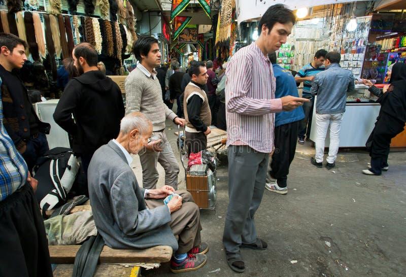 Verdienen de menigte jonge en bejaarde mensen en besteden geld in de bazaar stock afbeelding