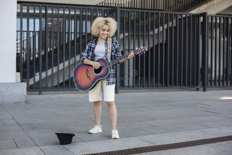 Verdient de vrouwen Afrikaans-Amerikaanse verschijning, straatmusicus geld door de gitaar te spelen stock foto's