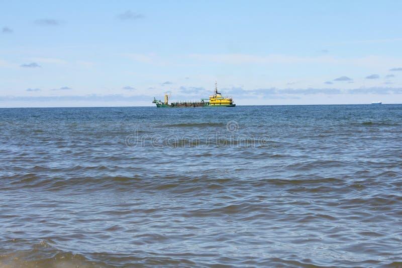 Verdieping van fairway op zee Baggermachine in actie stock foto
