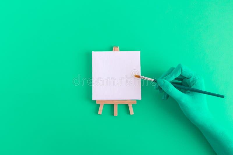 Verdissez la main colorée avec la brosse et la petite toile d'art vide sur le concept d'abrégé sur chevalet photographie stock libre de droits