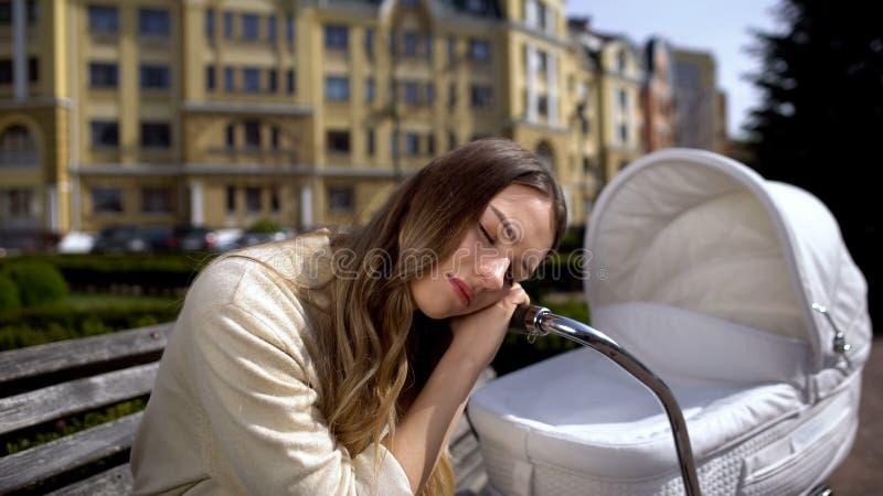 Verdoken moeder slaapt op pasgeboren koets op bank, uitputting stock foto's