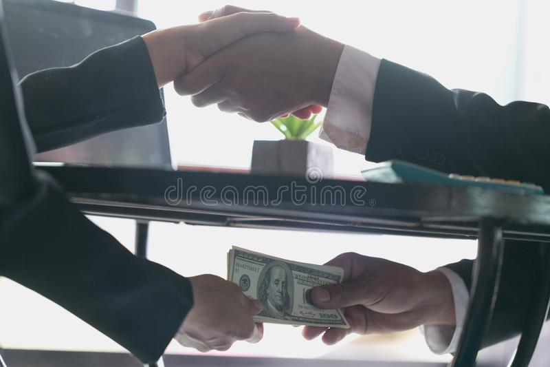 Verdorbener Geschäftsmann, der das Abkommen mit einem Händedruck versiegelt und ein Bestechungsgeld, eine Antibestechung und Korr lizenzfreie stockfotografie