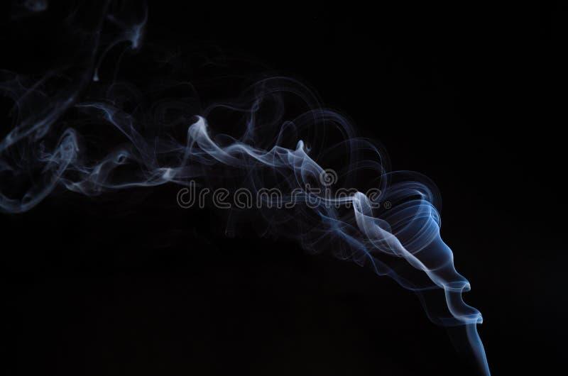 Verdraaide rook op zwarte stock afbeelding