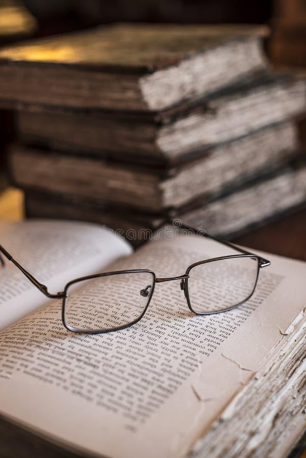 Verdrahten Sie gestaltete Lesebrille auf dem Stillstehen auf Seiten des offenen Buches mit Weinlese, alte Bücher im Hintergrund stockfotografie