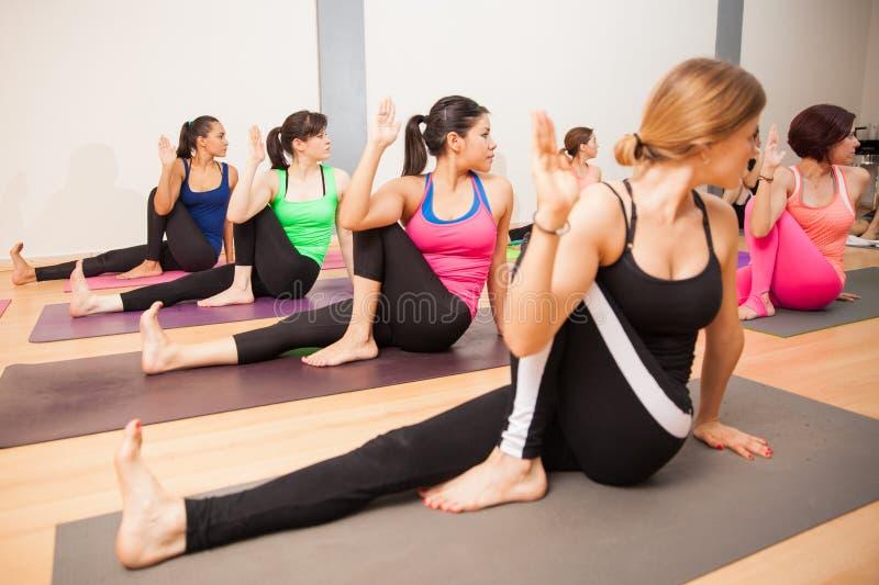 Verdrehen der weisen Haltung in der Yogaklasse lizenzfreie stockbilder