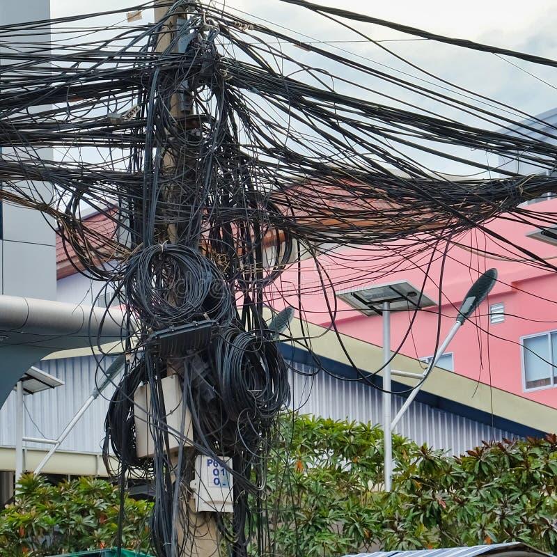 Verdrehte Drähte von Stromleitungen, Chaos von städtischen Kommunikationen, Kabelbündel stockfotos