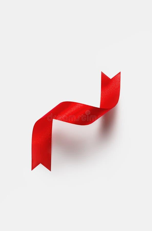 Verdrehte rote Form des Bandes Z des Satins teilte vertikale Fahne auf Weiß stockbild
