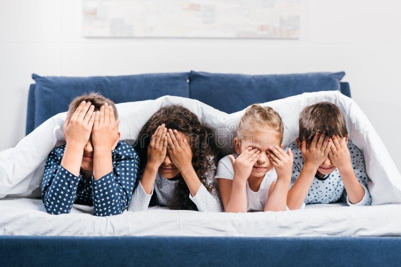 verduisterde mening die van multiculturele kinderen ogen behandelen terwijl het liggen in bed onder deken royalty-vrije stock foto's