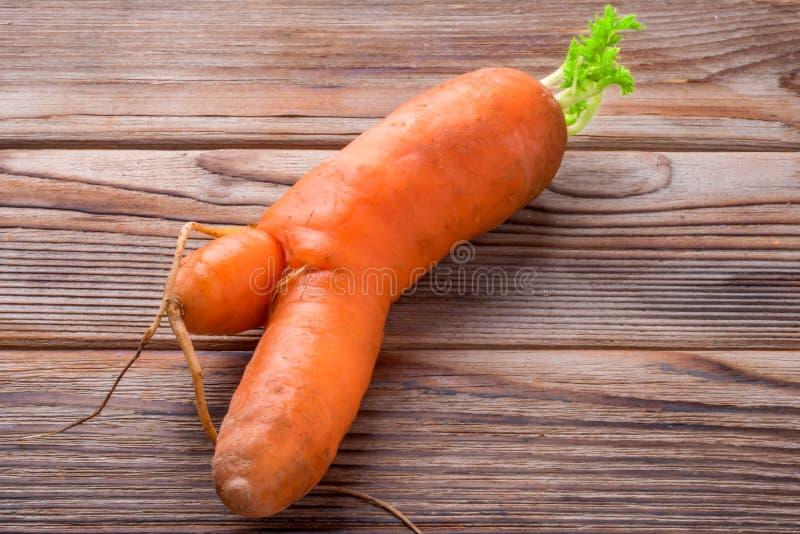 Verdura fea con la zanahoria doble en fondo de madera imagenes de archivo